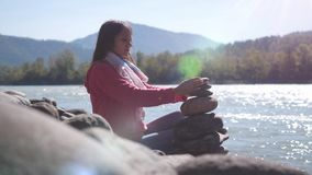 Young brunette woman putting pebble stack next to the mountain river on sunny day Royalty Free Stock Photography