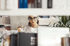 Young brunette woman reading book in a book store. View from shelf. royalty free stock images