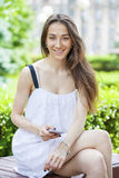 Young brunette woman reading a message on the phone Royalty Free Stock Images