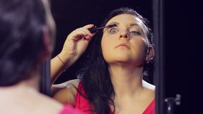 A young brunette woman in a red dress in front of a mirror makes eye makeup with black mascara. Close-up stock footage