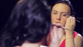A young brunette woman in a red dress in front of a mirror makes eye makeup with light shadows. Close-up stock footage
