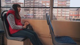 Girl rides the tram and listening to music. Young brunette woman in red sleeveless jacket listen to music on smartphone during tram ride.Girl looks out window stock video
