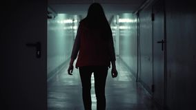 Young brunette woman in red sleeveless jacket is walking long dark corridor stock video footage