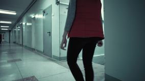 Young brunette woman in red sleeveless jacket is walking long dark corridor stock footage
