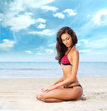A young brunette woman in a red swimsuit on the beach Stock Photo