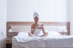 Young brunette woman relax with coffee in bed Stock Photography