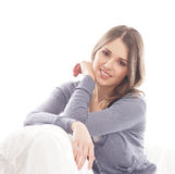 A young brunette woman relaxing in a blue sweater Royalty Free Stock Image