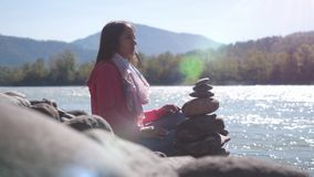 Young brunette woman relaxing by pebble stack next to the mountain river Stock Image