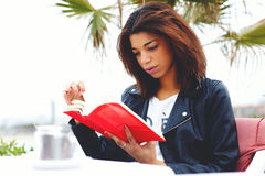 Young brunette woman relaxing at weekend while read interesting book outdoors in cafe restaurant Royalty Free Stock Images