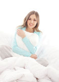 A young brunette woman relaxing in a white bed Royalty Free Stock Photography