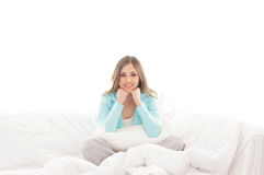 A young brunette woman relaxing in a white bed Stock Photography
