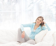 A young brunette woman relaxing in a white bed Royalty Free Stock Photos
