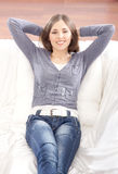 A young brunette woman relaxing on a white sofa Stock Images