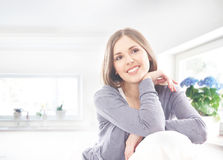 A young brunette woman relaxing on a white sofa Stock Photography