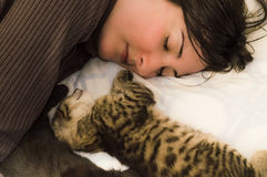 Young brunette woman resting with cute kittens on the bed. Royalty Free Stock Images