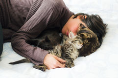 Young brunette woman resting with three cute kittens on the bed. Stock Photo
