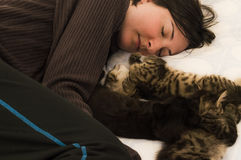 Young brunette woman resting with three cute kittens on the bed. Royalty Free Stock Photo