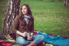 Young brunette woman resting under a tree Stock Images