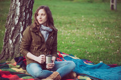 Young brunette woman resting under a tree Royalty Free Stock Photo