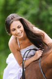 Young brunette woman rides a horse Stock Photography