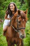 Young brunette woman rides a horse Stock Photo