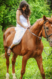 Young brunette woman rides a horse Royalty Free Stock Images