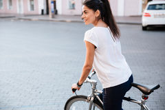Young brunette woman riding on bicycle in city stock photos