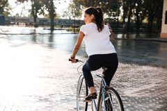 Young brunette woman riding on bicycle in city street royalty free stock photography