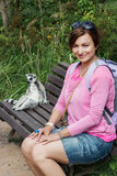 Young brunette woman and Ring-tailed lemur sitting on the bench Stock Images