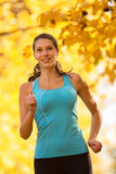 Young brunette woman running in autumn forest Stock Photos