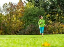 Young brunette woman running in park. Royalty Free Stock Images