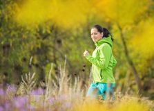 Young brunette woman running in park. Stock Photos