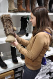 A young brunette Woman shopping for boots Stock Photography