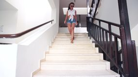 Young brunette woman in shorts, sunglasses down the stairs to hotel in summer. holiday and vacation stock video
