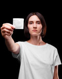 A serious young woman showing a packed condom on a black background. Healthy lifestyle concept. Copy space. AIDS Stock Photos