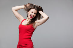 Young brunette woman showing devil horns hand gesture posing in studio. Young brunette woman showing devil horns hand gesture posing in studio Royalty Free Stock Photo