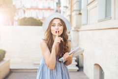Young brunette woman showing silence sign with finger on lips Royalty Free Stock Images