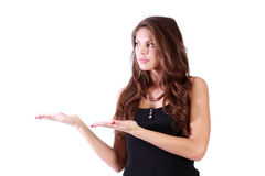 Young brunette woman shows and looks to left Royalty Free Stock Image