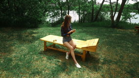 Young brunette woman sits outdoors and surfing internet with mobile phone at the park stock video
