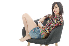 Young brunette woman sitting in a armchair with a phone. Isolated on white background Stock Image