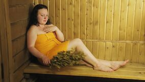 A young brunette woman is sitting in a bath with a broom wrapped in a towel