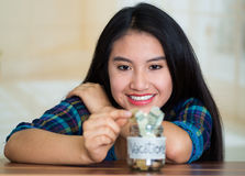 Young brunette woman sitting down facing camera, putting coins inside glass jar with money inside, label reading Royalty Free Stock Images