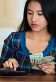 Young brunette woman sitting down facing camera, using calculator and holding stack of dollar bills Royalty Free Stock Images