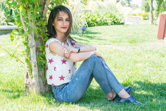 Young brunette woman sitting on the lawn under a tree Stock Photography