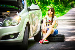 Young brunette woman sitting near a silver car on the roadside with a broken wheel Stock Images