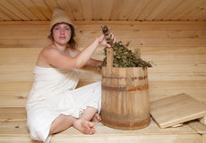Young brunette woman sitting in sauna Stock Photo