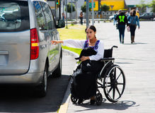 Young brunette woman sitting in wheelchair smiling with positive attitude, holding out arm looking for taxi, outdoors Stock Photos