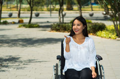 Young brunette woman sitting in wheelchair smiling with positive attitude, outdoors environment, physical recovery Royalty Free Stock Photos