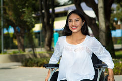 Young brunette woman sitting in wheelchair smiling with positive attitude, outdoors environment, physical recovery Stock Images