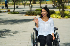 Young brunette woman sitting in wheelchair smiling with positive attitude, outdoors environment, physical recovery. Concept Royalty Free Stock Photos